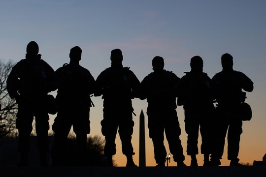 National Guard soldiers are seen in silhouette as they keep guard in front of the Capitol Building and near the Washington Monument in Washington on Jan. 19, 2021, ahead of the 59th inaugural ceremony for President-elect Joe Biden and Vice President-elect Kamala Harris. (Roberto Schmidt/AFP via Getty Images)