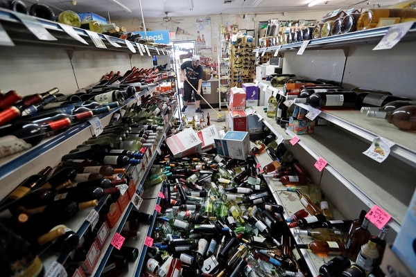 Bottles of wine are strewn in the middle of an aisle as Victor Abdullatif, background center, mops inside of the Eastridge Market, his family's store, Saturday, July 6, 2019, in Ridgecrest, Calif. (Marcio Jose Sanchez/AP)