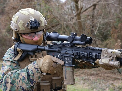 Chief Warrant Officer 4 Dave Tomlinson, infantry weapons officer at Marine Corps Systems Command, demonstrates the Squad Common Optic attached to the M27 Infantry Automatic Rifle. (Matt Gonzales/Marine Corps)