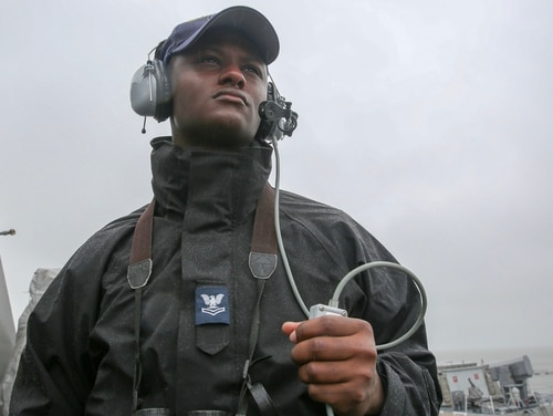 Operations Specialist Seaman Demetrus Jones from the guided-missile destroyer Truxtun shows how the black Gortex parka (with a second class petty officer tab) pairs with the the flame-resistant, two-piece organizational clothing prototype in the navy blue variant. U.S. Fleet Forces Command will conduct a second test of the prototype later this year. The goal of the initiative is to provide a no-cost, safe, and comfortable organizational clothing option to the improved, flame-resistant variant (IFRV) coverall. (Mass Communication Specialist 2nd Class Stacy M. Atkins Ricks/Navy)