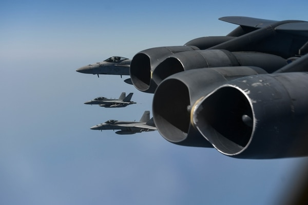 U.S. Navy strike fighters form up off the wing of a U.S. Air Force B-52H Stratofortress assigned to the 20th Expeditionary Bomb Squadron, and part of the Bomber Task Force deployed to the region conduct joint exercises on June 1 (Staff Sgt. Erin Piazza/Air Force)