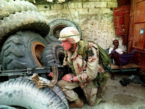A Somali man sits back and smokes Aug. 31, 1993, as a U.S. soldier guards the front gate of a garage that was being searched for arms. (Alexander Joe/AFP via Getty Images)