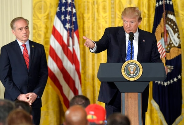 President Donald Trump, right, standing with Veterans Affairs Secretary David Shulkin, left, speaks during a bill signing event for a Veterans Affairs Accountability measure at the White House on June 23, 2017. Lawmakers said Wednesday that drama surrounding Shulkin's job status is hurting VA reform efforts in Congress. (Susan Walsh/AP)