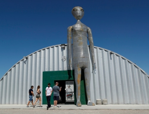 People enter and exit the Alien Research Center in Hiko, Nev. No one knows what to expect, but lots of people are preparing for