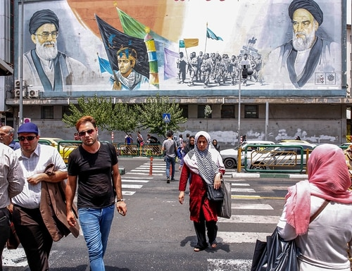People cross a street past a mural depicting former and current Supreme Leaders Ayatollah Ruhollah Khomeini, right, and Ayatollah Ali Khamenei, left, with other scenes in the Iranian capital Tehran on July 22, 2019. (AFP via Getty Images)