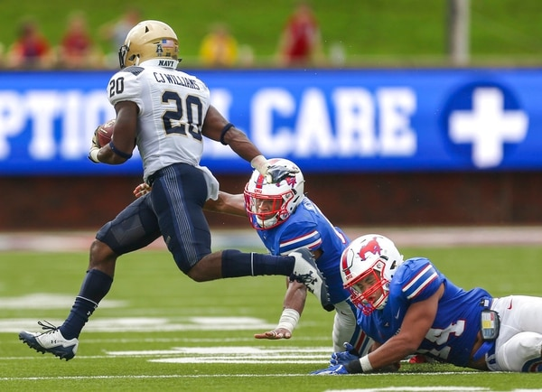 SMU linebacker Richard Moore and safety Elijah McQueen try to bring down Navy tight end CJ Williams during the second quarter of Saturday's game at Gerald J. Ford Stadium in Dallas. (Ryan Michalesko/The Dallas Morning News via AP)