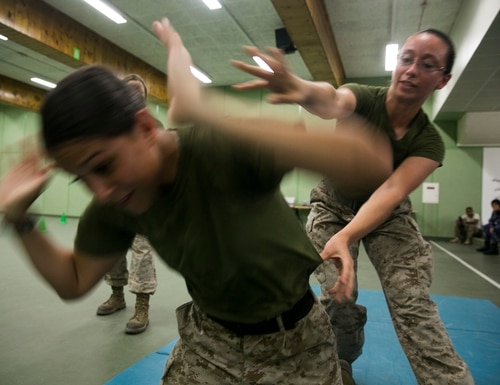 QATAR (Aug 18, 2015) U.S. Marines Cpl. Justine Woodend, left, and Lance Cpl. Chevon Ferrel demonstrate searching techniques during a subject matter expert exchange with the Qatari Internal Security Forces Female VIP Protection Unit in Qatar. Woodend is a motor transportation operator and Ferrel is an ammunition technician with the 15th Marine Expeditionary. They are members of the Female Partner Force Engagement Team. The FPFET was comprised of U.S. Marines with the 15th MEU as well as Soldiers and Sailors with Special Operations Command Central-Forward and Joint Special Operations Task Force-Arabian Peninsula. During the SMEE they covered medical care, marksmanship, and personal security detail strategies. (U.S. Marine Corps photo by Cpl. Anna Albrecht/Released)