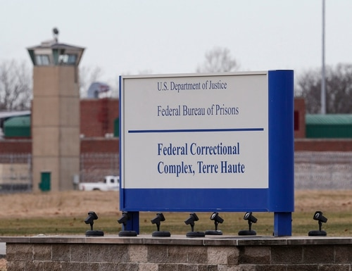 In this Dec. 10, 2019, file photo the guard tower flanks the sign at the entrance to the U.S. Penitentiary in Terre Haute, Ind. (Michael Conroy/AP)