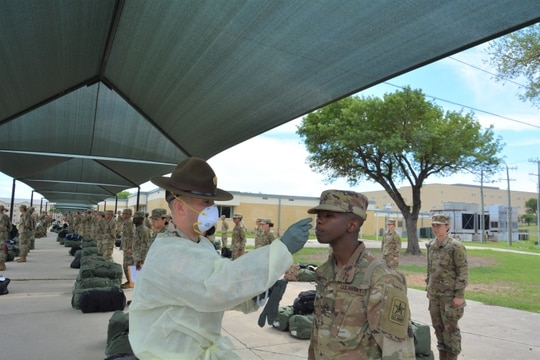 A drill sergeant takes the temperature of a 68W Combat Medic arriving from Fort Sill, OK to begin their advanced individual training at Fort Sam Houston, TX. (Army)