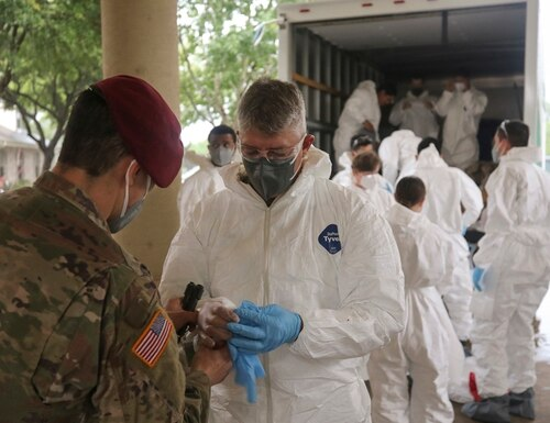 Army National Guard Spc. Joel Mendoza assists Capt. Patrick Couch with donning personal protective gear in preparation for disinfecting the West Oaks Nursing and Rehabilitation Center in Austin, Texas, May 12, 2020. (Staff Sgt. Michael Giles/Army National Guard)