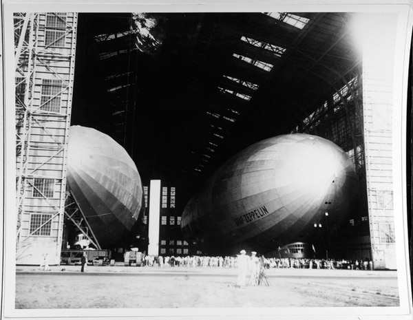 At right, the German dirigible Graf Zeppelin (LZ-127) in the airship hangar at Naval Air Station Lakehurst, New Jersey. Photo is dated 7 August 1929. Also in the hangar is the U.S. Navy's dirigible Los Angeles (ZR-3), which had been built in Germany as Zeppelin airship LZ-126. (Courtesy of the San Francisco Maritime Museum, 1969, now in the collections of U.S. Naval History and Heritage Command)