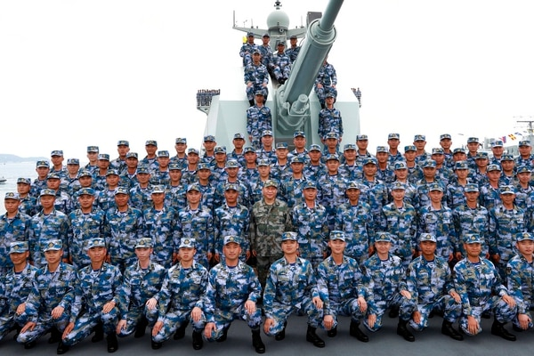 In this April 12, 2018, file photo released by Xinhua News Agency, Chinese President Xi Jinping, center in green military uniform, poses with soldiers on a navy ship for a photo after he reviewed the Chinese People's Liberation Army (PLA) Navy fleet in the South China Sea. (Li Gang/Xinhua via AP)