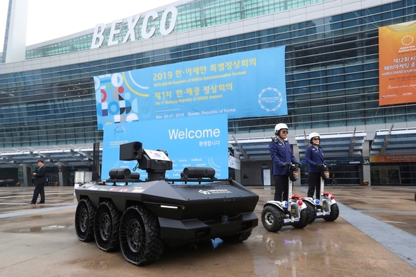 South Korean police officers pass by an HR-Sherpa unmanned ground vehicle on display in Busan, South Korea, on Nov. 24, 2019. (Ahn Young-joon/AP)