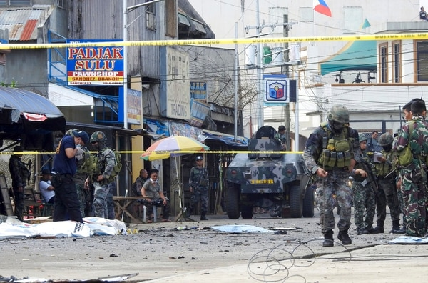 Police investigators and soldiers outside a Roman Catholic cathedral in Jolo on Jan. 27 after two bombs killed 23 people and wounding nearly 100 others during a Sunday Mass, officials said. (Nickee Butlangan/AP)