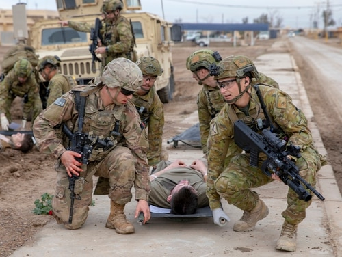 A U.S. soldier, left, and Australian soldiers carry a simulated casualty on a Talon Litter during a mass casualty training exercise at Camp Taji, Iraq, Feb. 1, 2020. (Spc. Caroline Schofer/Army)