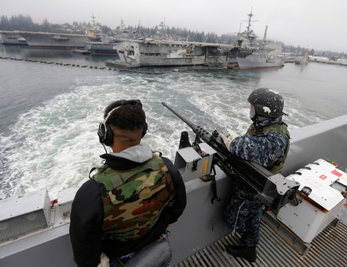 In this Jan. 13, 2015, file photo, two sailors on board the John Stennis aircraft carrier watch as the warship leaves Naval Base Kitsap in Washington state. (Ted S. Warren/AP)