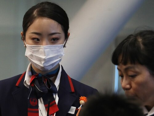 A Japan Airlines worker, left, wears a face mask while working inside a terminal at Los Angeles International Airport on Jan. 23, 2020, in Los Angeles. Defense and Health and Human Services officials said this week that everyone has a