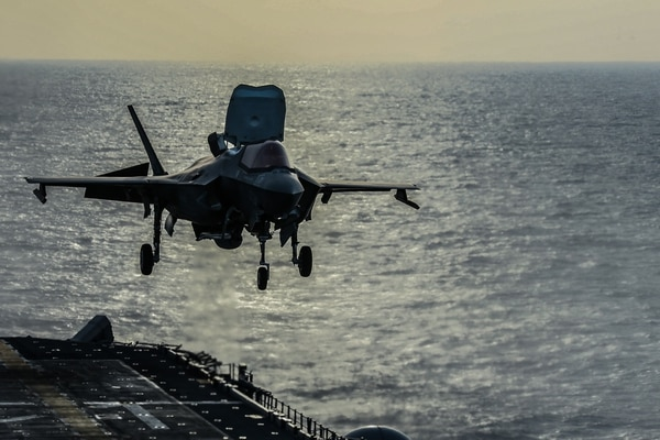 An F-35B Lightning II fighter aircraft with Marine VMM-265 prepares to land on the flight deck of the amphibious assault ship America. The Navy has used its amphibious assault ships to test the notion of smaller carriers. (Marine Corps photo by Lance Cpl. Kolby Leger)