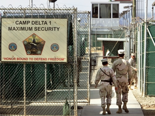 In this June 27, 2006 file photo, reviewed by a U.S. Department of Defense official, U.S. military guards walk within Camp Delta military-run prison, at the Guantanamo Bay U.S. Naval Base, Cuba. (Brennan Linsley/AP)