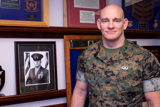 The 19th Sergeant Major of the Marine Corps, Sgt. Maj. Troy E. Black, poses for a photo with a photograph of the 8th Sergeant Major of the Marine Corps, Sgt. Maj. John R. Massaro (retired), at Headquarters Marine Corps, Va., May 21, 2020. (Sgt. Victoria Ross/Marine Corps)