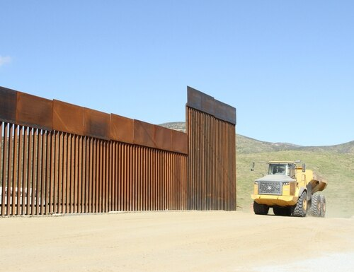 A dump truck hauls excavated debris in front of unfinished portions of a secondary border wall near San Diego, Calif., on March 28, 2019. (Brooks Hubbard IV/U.S. Army)