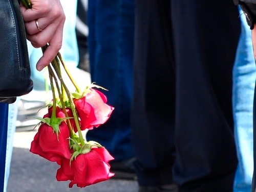 A woman holds roses as she and others gather for the funerals of five Russian nuclear engineers killed by a rocket explosion in Sarov, the closed city which has served as a base for Moscow's nuclear weapons program since the late 1940s. (Russian State Atomic Energy Corporation ROSATOM via AP)