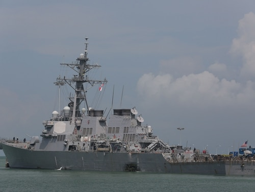 The destroyer John S. McCain is shown moored pier side at Changi Naval Base, Singapore, following a collision with the merchant vessel Alnic MC on Monday. (Grady T. Fontana/Navy)
