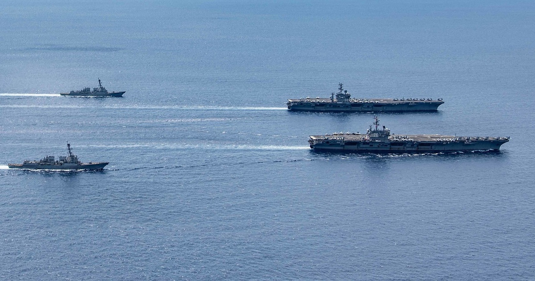 The carriers Ronald Reagan and Nimitz carrier strike groups steam in formation. (MC3 Jason Tarleton/U.S. Navy)