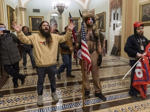 In this Jan. 6, 2021, file photo, supporters of President Donald Trump are confronted by U.S. Capitol Police officers outside the Senate Chamber inside the Capitol in Washington. Jacob Anthony Chansley, a Navy veteran whom officials have identified as the man with the painted face and wearing a horned headdress, was taken into custody Jan. 9, 2021, and charged with counts that include violent entry and disorderly conduct on Capitol grounds. (Manuel Balce Ceneta/AP)