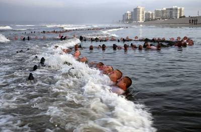 Navy SEAL candidates participate in surf immersion during Basic Underwater Demolition/SEAL (BUD/S) training at Naval Special Warfare (NSW) Center
