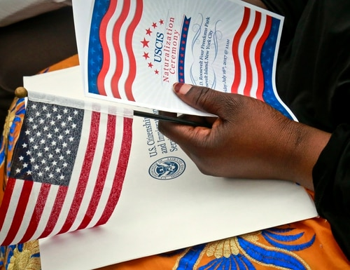 A new U.S. citizen holds a program and flag during U.S. Citizen and Immigration Services ceremony on June 16, 2017. (Bebeto Matthews/AP)