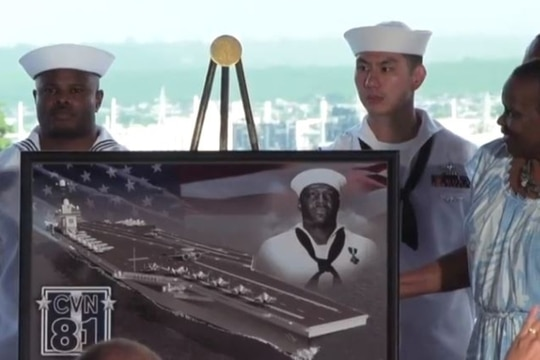 Members of Doris Miller's family gather around a portrait honoring the hero of Pearl Harbor and the future aircraft carrier that will bear his name. (Department of Defense)