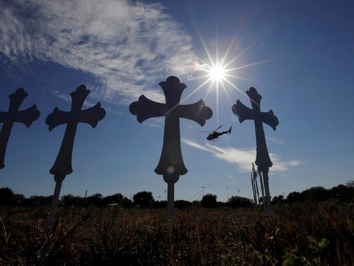 A law enforcement helicopter flies over crosses placed near the scene of a shooting at the First Baptist Church of Sutherland Springs. (Eric Gay/AP)