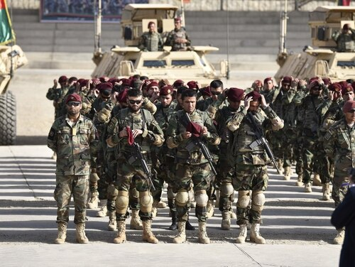 Recently graduated soldiers don the distinctive maroon beret of the commando upon completion of the graduation ceremony on Camp Commando, Kabul, Afghanistan (U.S. Army Master Sgt. Felix A. Figueroa/NATO)