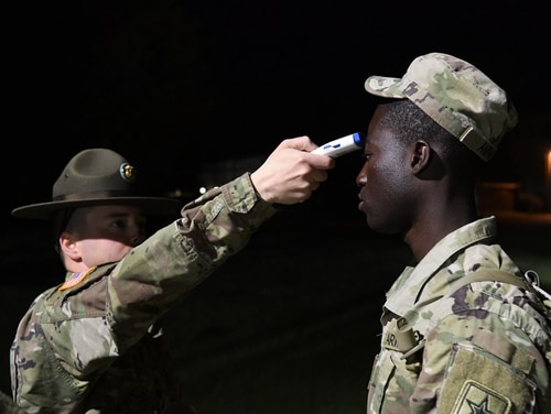 A drill sergeant takes the temperature of a soldier before he boards a bus March 31, 2020 after graduating basic training at Fort Jackson, South Carolina. (Alexandra Shea/Army)