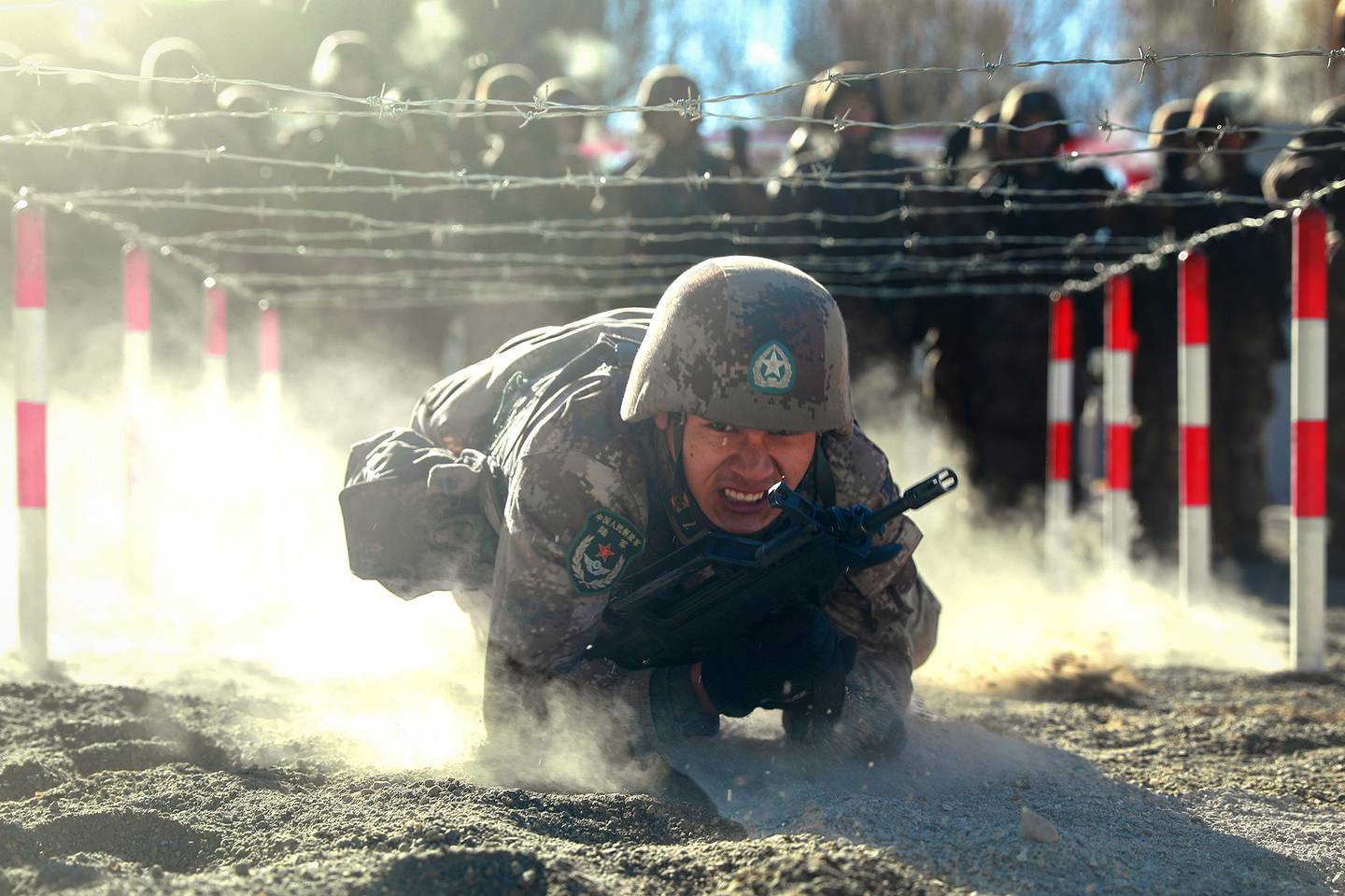 A Chinese soldier low-crawls in the dirt under barbed wire during training.