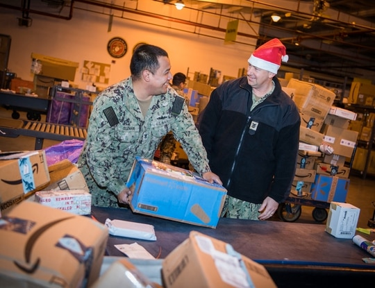 Navy Logistics Specialist 3rd Class Rogelio Guzman shows Naval Station Rota, Spain's Command Master Chief Gary Rosenbaum, how to sort mail, Dec. 10, 2019. (Mass Communication Specialist 1st Class Benjamin Lewis/Navy)