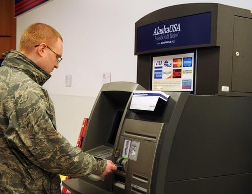 An airman inserts a bank card into an ATM Oct. 26, 2010, at Eielson Air Force Base, Alaska. (Air Force)
