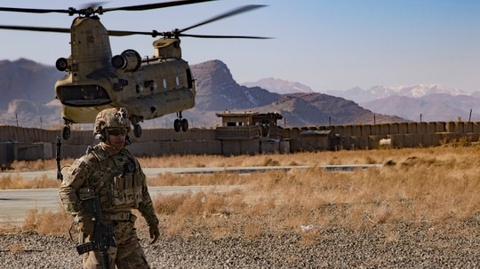 U.S. Army Capt. Bradley D. Rager, assigned to the Headquarters and Headquarters Battalion, 1st Armored Division, helps secure the helicopter landing zone as a CH-47 Chinook helicopter prepares to land at an Afghan military base Dec. 14, 2019, in southeastern Afghanistan. (Master Sgt. Alejandro Licea/Army)