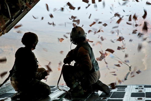 An Army psychological specialist and a Marine load master watch leaflets fall off of a KC-130 Super Hercules over southern Afghanistan, Aug. 28, 2013. Leaflets were dropped in support of operations to defeat insurgency influence in the area. (Sgt. Demetrius Munnerlyn/Marine Corps)