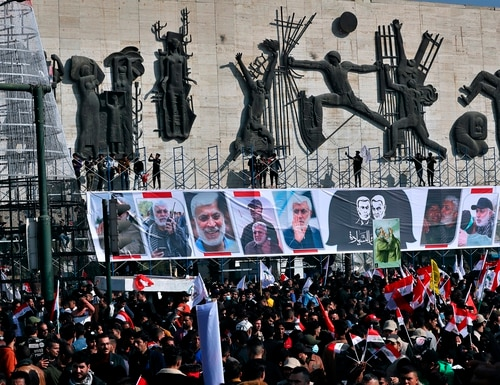 Supporters of the Popular Mobilization Forces hold a posters of Abu Mahdi al-Muhandis, deputy commander of the Popular Mobilization Forces, front, and Gen. Qassem Soleimani, head of Iran's Quds force during a protest, in Tahrir Square, Iraq, Sunday, Jan. 3, 2021. (Khalid Moha/AP)