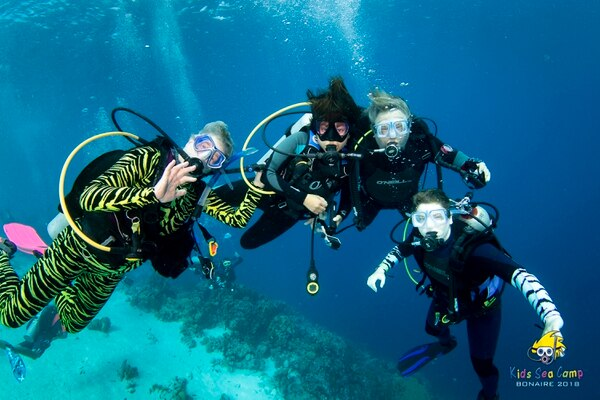 This November 2018 photo provided by Margo Peyton shows, from left, Diana Ademic, Berenice Felipa, Steve Salika and Tia Salika enjoying a dive during their 2018 Thanksgiving vacation trip at a Kids Sea Camp week at Buddy Dive Resort off Bonaire, a Netherlands-administered island in the Leeward Antilles off the coast of Venezuela. All four were on board the dive boat Conception and all died in the fire that swept the vessel. (Margo Peyton via AP)