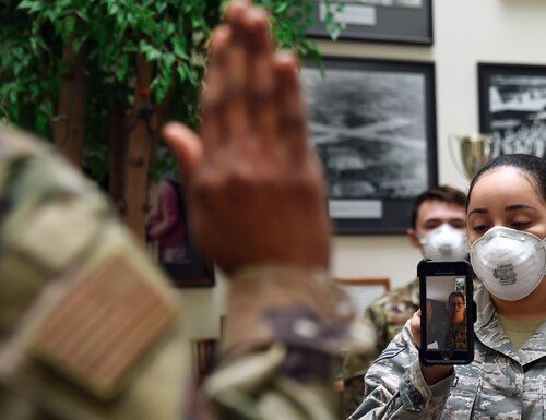 Maj. Yaira Nevarez, left, administers the oath of enlistment to Staff Sgt. Jennifer Rogers during a virtual reenlistment at Hanscom Air Force Base, Mass. (Linda LaBonte Britt/Air Force)