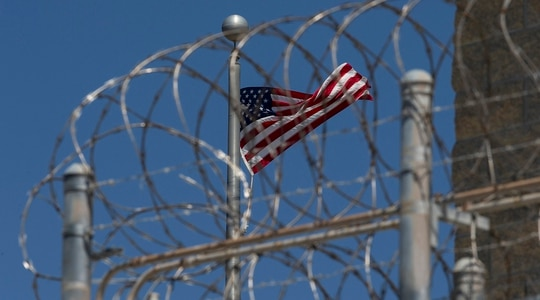 In this April 17, 2019, file photo reviewed by U.S. military officials, a U.S. flag flies inside the razor wire of the Camp VI detention facility, Wednesday, April 17, 2019, in Guantanamo Bay Naval Base, Cuba. (Alex Brandon/AP)
