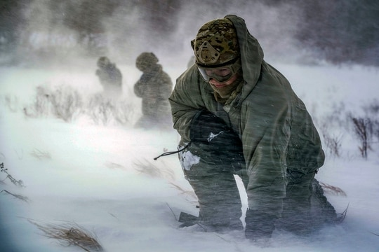 Staff Sgt. Benjamin Reynolds, 891st Missile Security Forces Squadron response force leader, crouches in rotor wash during a field training exercise at Turtle Mountain State Forest, N.D., Feb. 14, 2018. During the exercise 91st Security Forces Group defenders coordinated simulated medical evacuations with two 54th Helicopter Squadron UH-1N Iroquois. (Senior Airman J.T. Armstrong/Air Force)