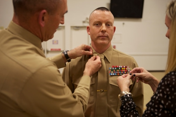 U.S. Marine Corps Lt. Col. Christopher G. Dixon, center, operations officer, 2nd Marine Division (2nd MARDIV) is promoted to the rank of colonel by U.S. Marine Corps Brig. Gen. James W. Lukeman, commanding general, 2nd MARDIV, and Erin, Dixon's spouse, at Camp Lejeune, N.C., Jan. 3, 2014. The ceremony was held to promote Dixon to the rank of colonel. (U.S. Marine Corps photo by Lance Cpl. David McKenzie, 2nd MARDIV, Combat Camera/Released)