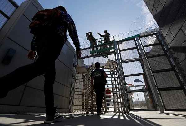 Marines install concertina wire, above, as pedestrians leave the United States for Mexico at the San Ysidro port of entry Friday, Nov. 16, 2018, in San Diego. (Gregory Bull/AP)