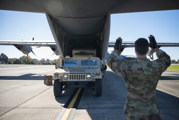 Airman 1st Class Nicholas Mariner, a loadmaster with the 61st Airlift Squadron, directs a Humvee into a C-130J Super Hercules at Fort Knox, Ky., in support of Operation Faithful Patriot on Oct. 29, 2018. (Airman 1st Class Zoe M. Wockenfuss/Air Force)