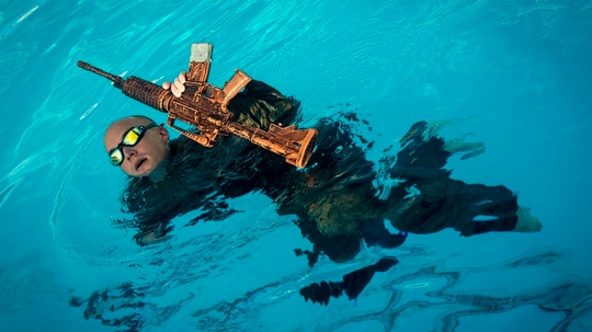 A Marine swims with a rifle during a reconnaissance screener test at the Camp Hansen pool, Okinawa, Japan, June 29, 2018. The screener evaluated the MarinesÕ performance in preparation for the Basic Reconnaissance Course through a series of physically demanding tests. (Pfc. Kaleb Martin/Marines)