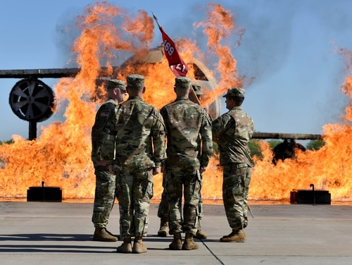 Army Capt. Christopher Gibbs, commander of Delta Company 169th Engineer Battalion, passes the guidon to Lt. Col. Aaron Boher, battalion commander, at the Department of Defense Fire Academy on Goodfellow Air Force Base, Texas, in April. The base has a combined population of 5,500 and may soon see as many as 20,000 undocumented immigrant children. (Senior Airman Randall Moose/Air Force)